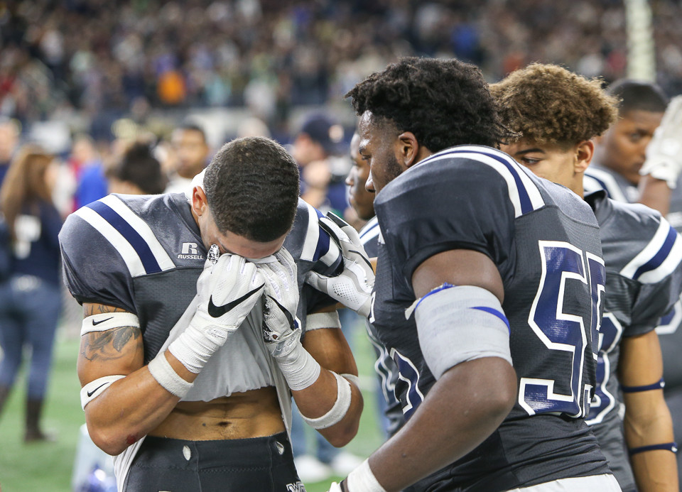 West Orange-Stark Mustangs teammates console each other following a 41-21 loss to Pleasant Grove in the UIL Class 4A Division II state football championship game at AT&T Stadium in Arlington, Texas, on December 22, 2017.