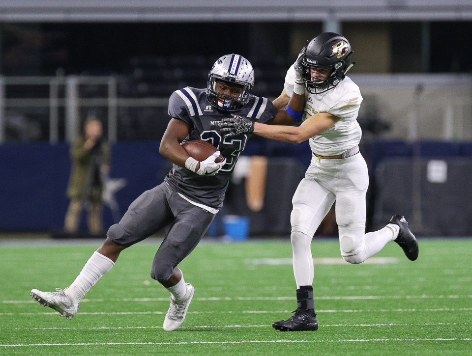 West Orange-Stark Mustangs junior Kayven Cooper (23) delivers a stiff arm to Pleasant Grove Hawks junior defensive back Ryan Pickelman (7) during the UIL Class 4A Division II state football championship game between West Orange-Stark High School and Pleasant Grove High School at AT&T Stadium in Arlington, Texas, on December 22, 2017.