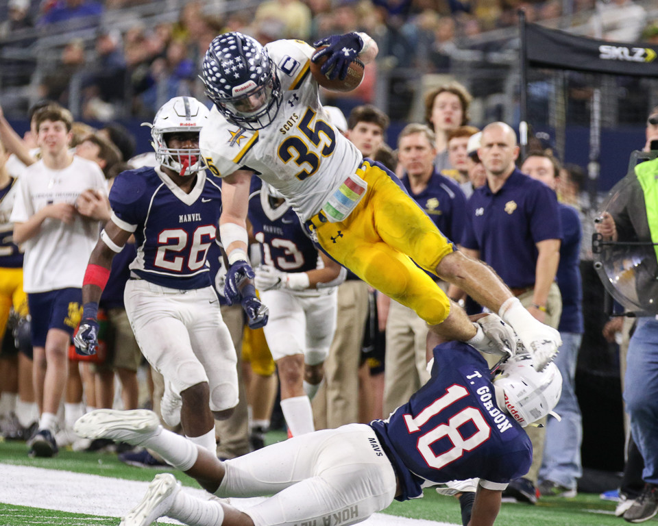 Highland Park Scots senior running back Paxton Alexander (35) leaps over Manvel Mavericks senior defensive back Trent Gordon (18) on a carry during the UIL Class 5A Division I state football championship game between Manvel High School and Highland Park High School at AT&T Stadium in Arlington, Texas, on December 22, 2017.