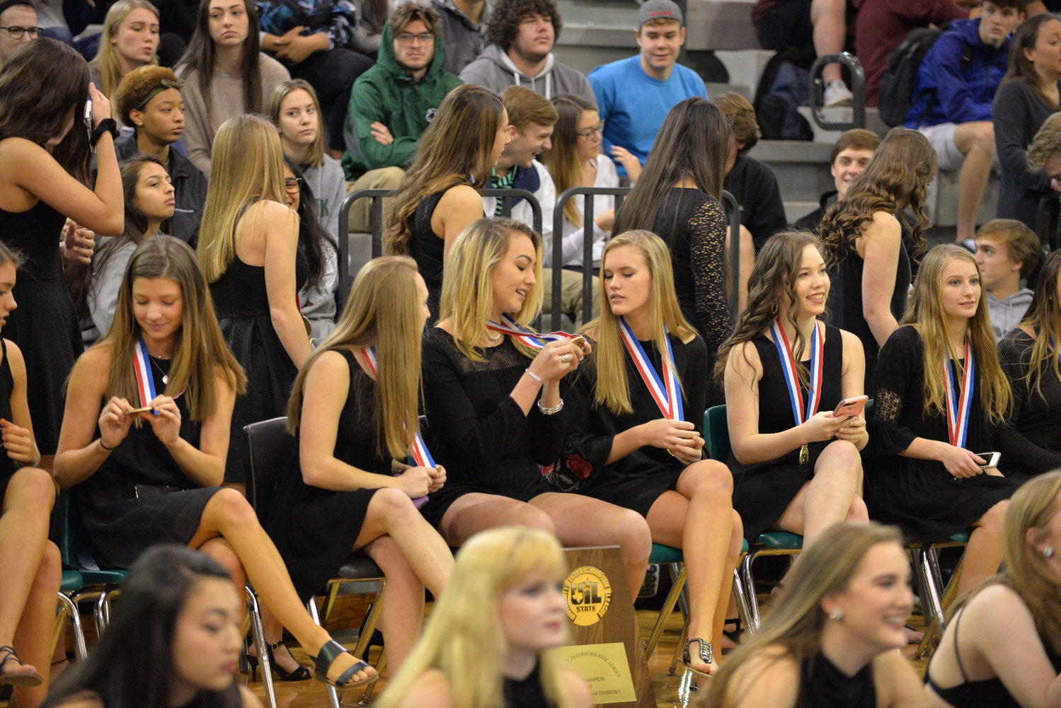 Cheerleaders compare UIL medals during the pep rally.