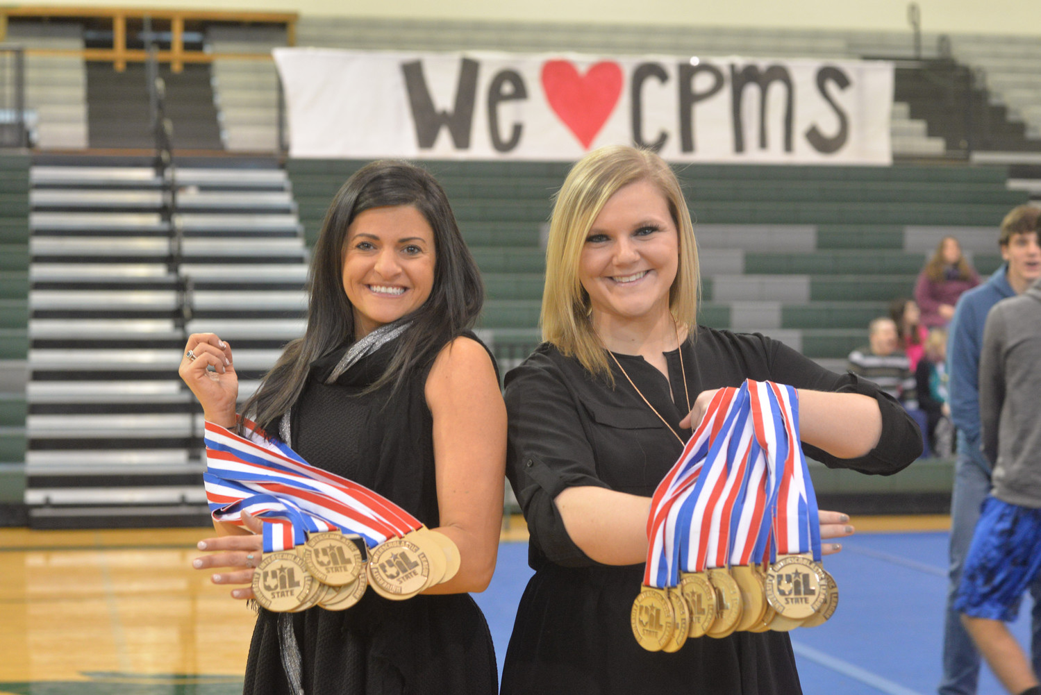 Cedar Park cheer sponsors Nadira King and Morgan Maddux hold UIL Spirit State championship medals at the CPHS cheer rally celebrating the team's state title, Tuesday, Jan. 23.