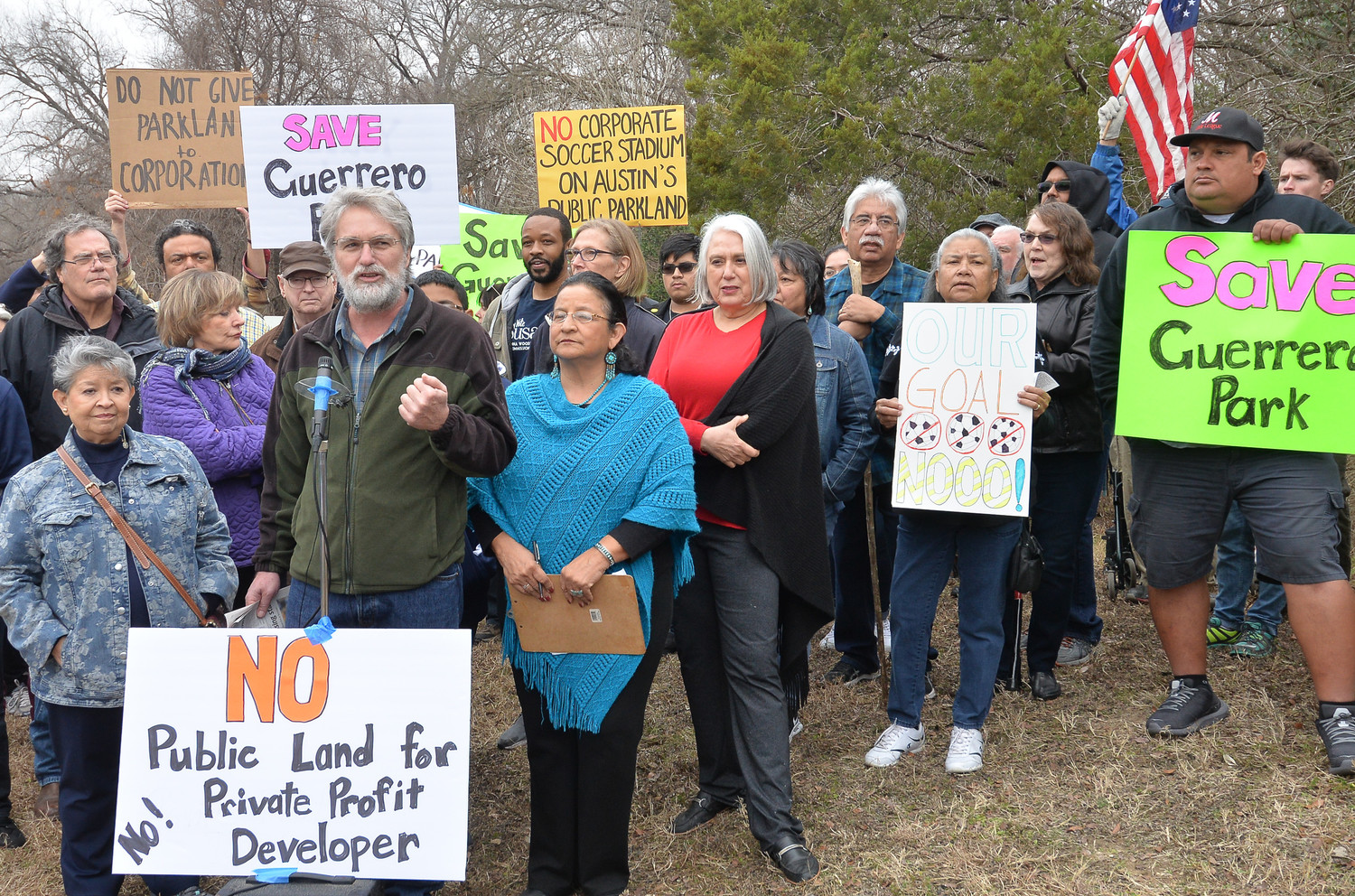 A large group gathered at the entrance to Roy G. Guerrero Metropolitan Park on Saturday afternoon to protest the use of public land to build an MLS soccer stadium.