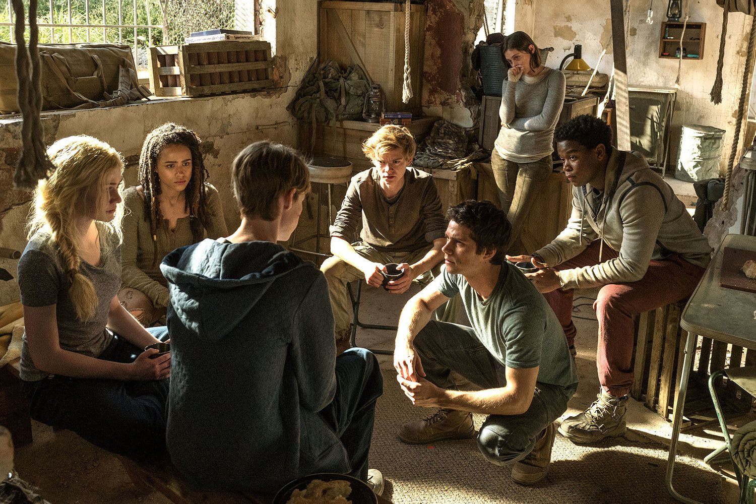 The group decides on their next move. (L-R) Sonya (Katherine McNamara), Harriet (Nathalie Emmanuel), Aris (Jacob Lofland, back to camera), Newt (Thomas Brodie-Sangster), Thomas (Dylan O'Brien), Brenda (Rosa Salazar), and Frypan (Dexter Darden) in Maze Runner: The Death Cure