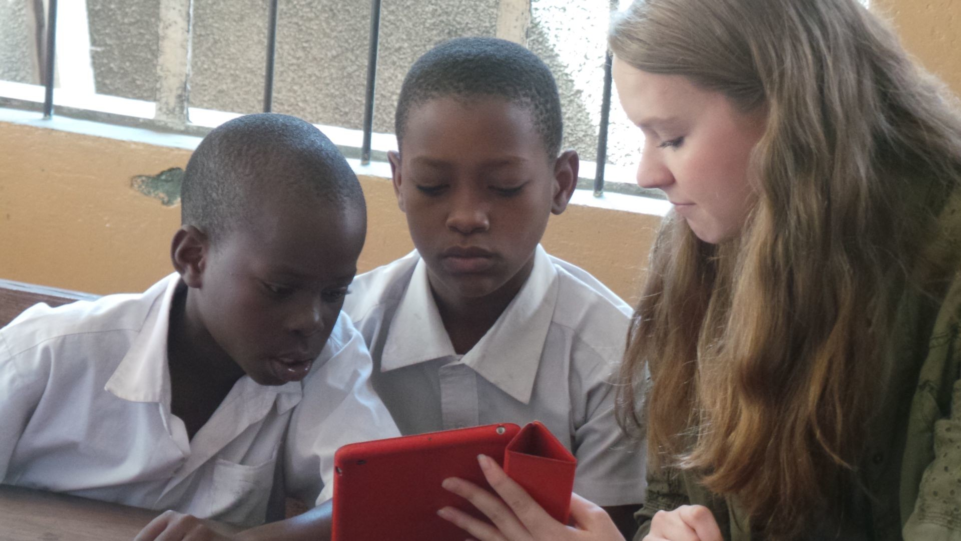 Reading Around The World Literacy Initiative founder, Carissa Mallory, teaches Tanzanian students how to use an iPad app.
