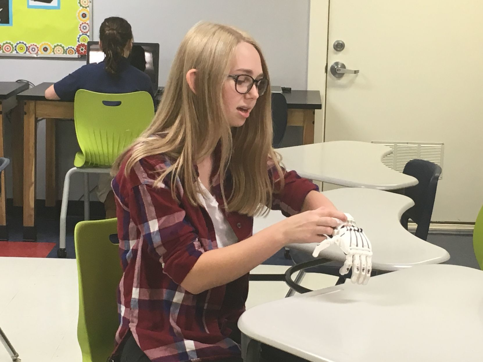 Paris Varnier, a senior at Summit Christian Academy, trying on her prosthetic hand.