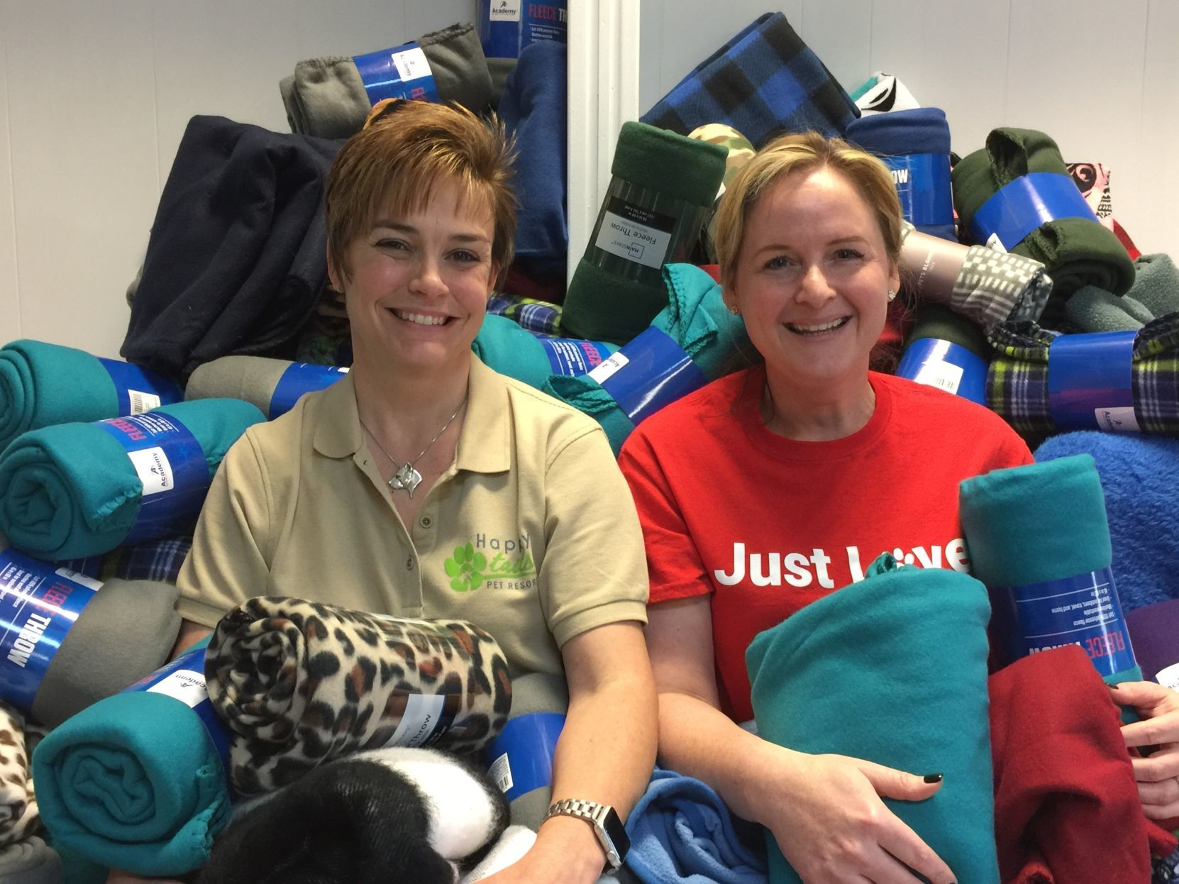 Brenda Tatro (left), owner of Happy Tails Pet Resort, and Kristen Huguley, executive director of Texas Humane Heroes, surrounded by mounds of donated blankets for homeless pets.
