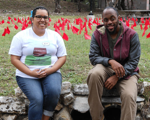 Concordia University Texas seniors Leslie Leal and Xzavier Beacham sit among red flags symbolizing the 1,800 college-age students that die annually as a result of drinking and driving. They are drawing awareness about solutions.