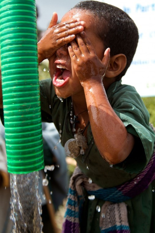 Alemitu, 6, dives into clean water for the first time during the dedication of her community's new well in Ethiopia.