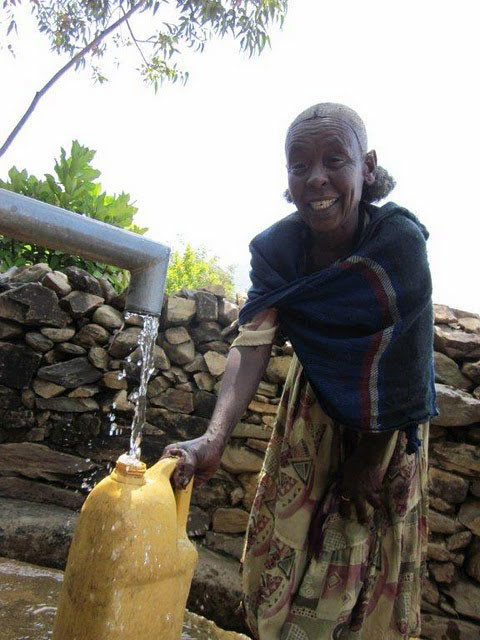 Water committee member Gidey fetches water at Mai-Shana II.