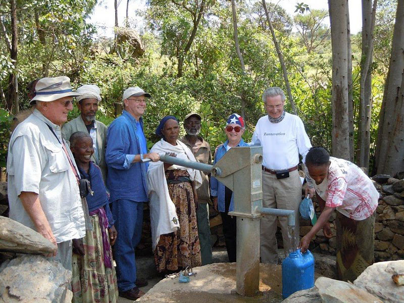 Moeller, with his hand on the pump, stands with his Water to Thrive team members and the local water committee at Mai-Shana I.