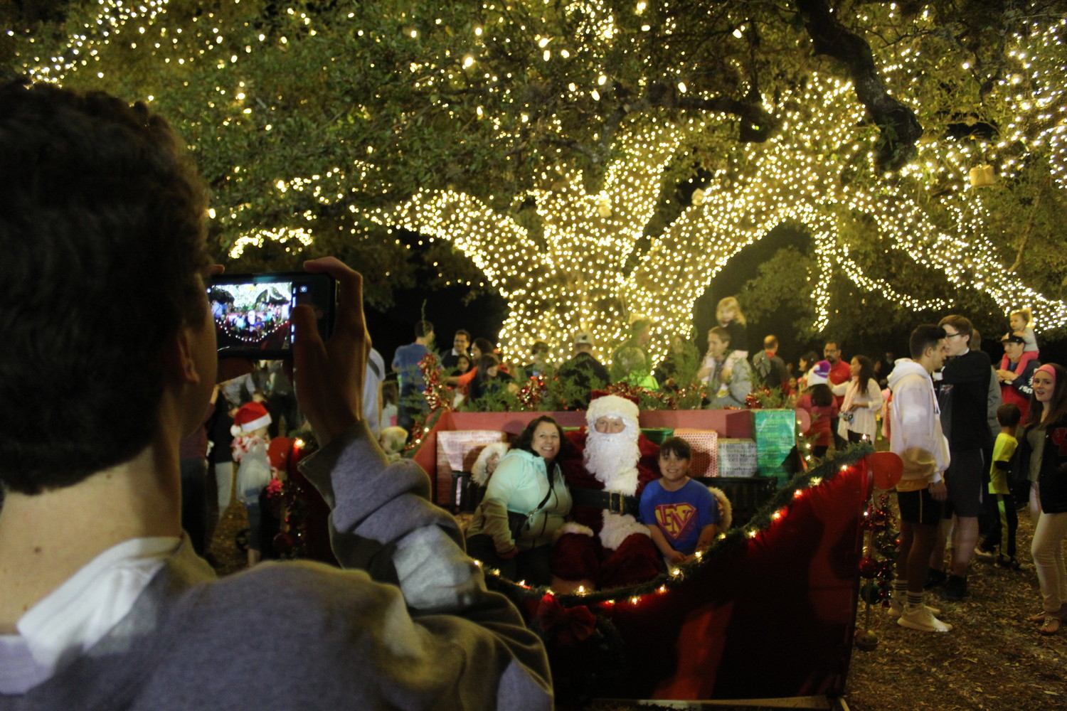 Underneath the glow of nearly 72,000 Christmas lights, a family poses for a photo with Santa, Friday, Dec. 1. The annual Tree Lighting and Santa's Workshop event in Cedar Park included free carriage rides, inflatable bounce houses, arts and crafts and caroling from the Cedar Park High School women's choir.