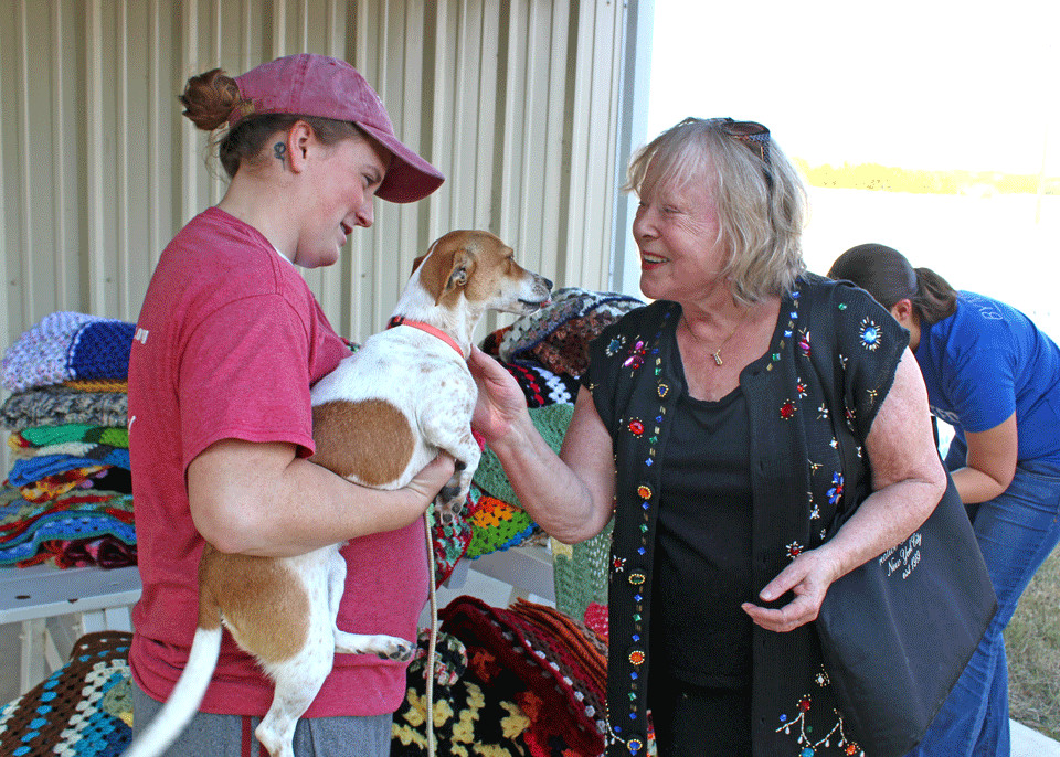 Jackie Bruce (left) holds adoptee Cayenne for Marita Rush (right) to pet as she brought in 100 blankets for Texas Humane Heroes animal shelter in Leander.