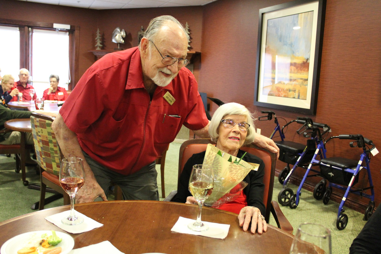 Andy Carver (left) and Billie Tips (right) pose after Carver surprised Tips with a bouquet of flowers during social hour at Lakeline Oaks in Cedar Park, Friday, Feb. 2.