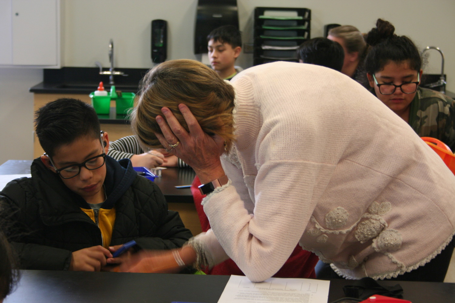 Teacher Patty Wirth assists deaf student Javier Compean during a science lab.