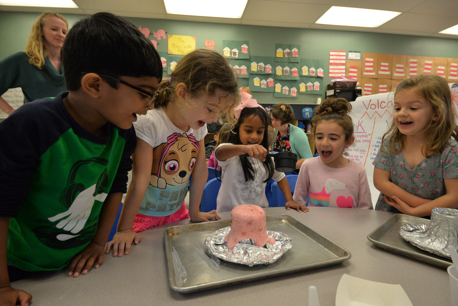 Awestruck students observe a re-creation of a volcano erupting using vinegar, baking soda, and food coloring.