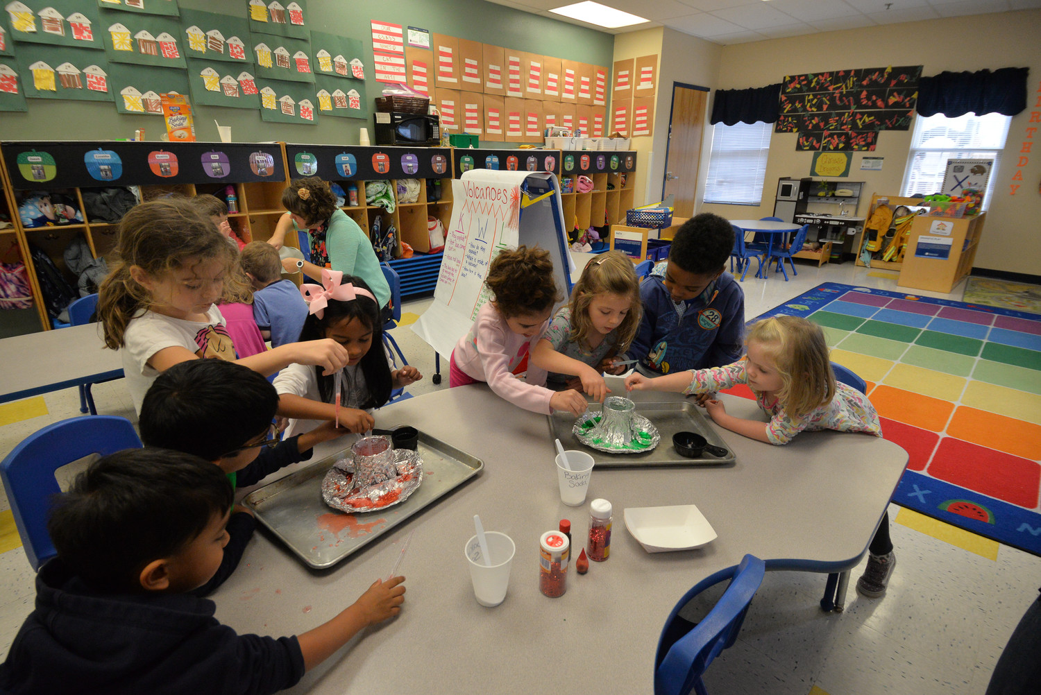Learning by doing, Goddard School students prepare to re-create an erupting volcano.