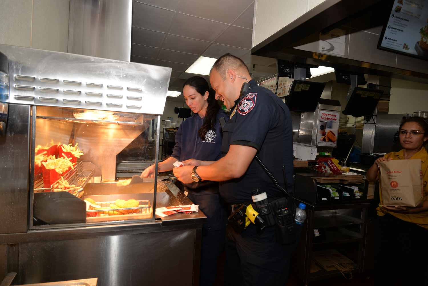 Cedar Park police officer David Camacho and Cedar Park firefighter Brenda Bonja prepare fries for customers at McDonalds.