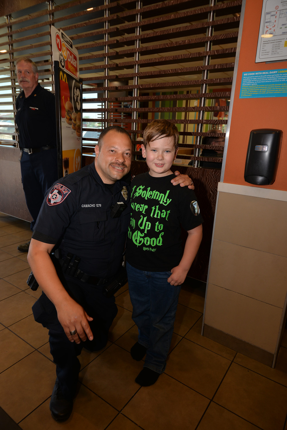 Cedar Park Police Officer David Camacho gets a hug from a fan while raising funds for the 100 Club of Central Texas.