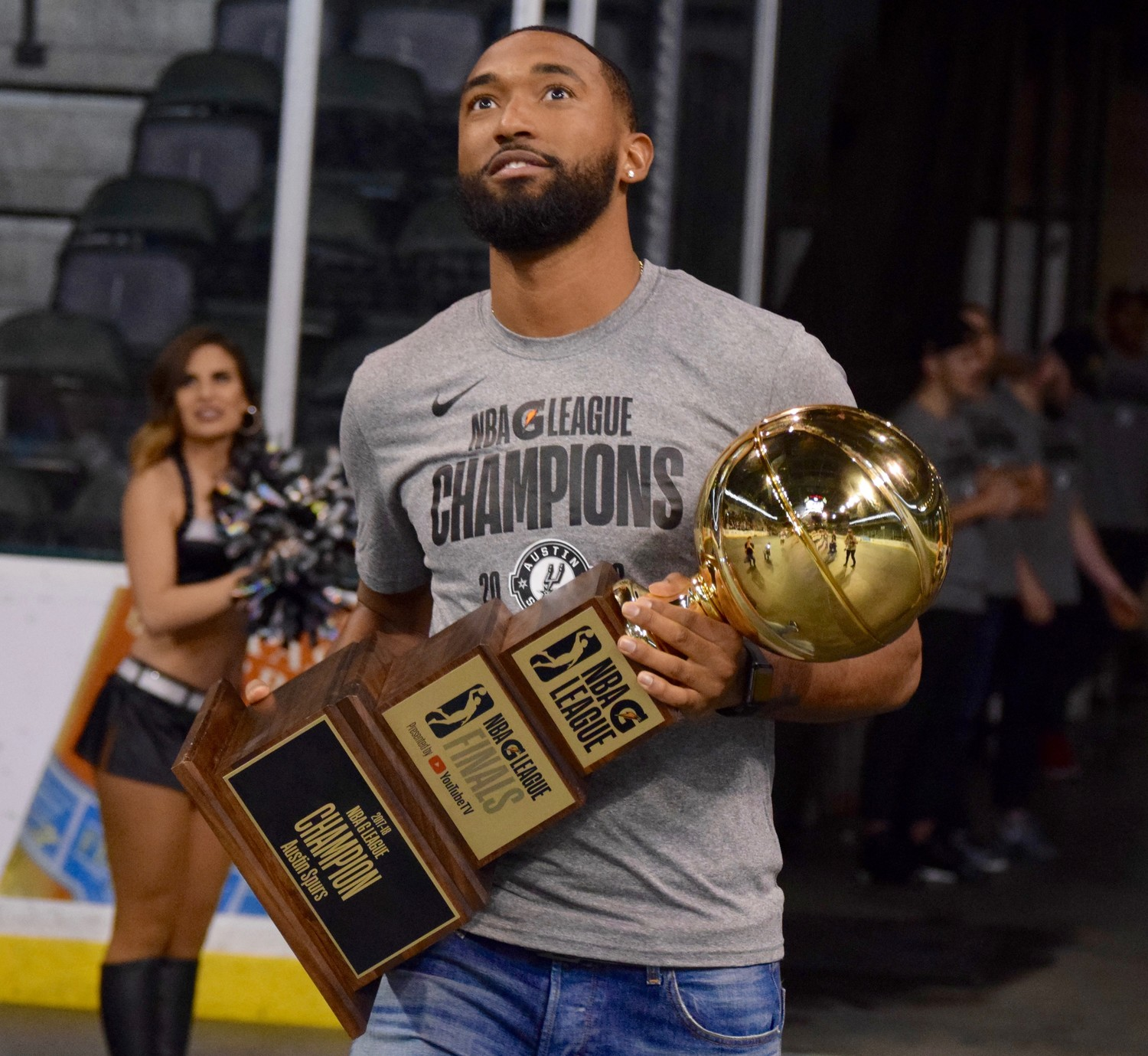 Spurs guard Darrun Hilliard carries the G League Championship to the stage at the Austin Spurs Celebration at the HEB Center.