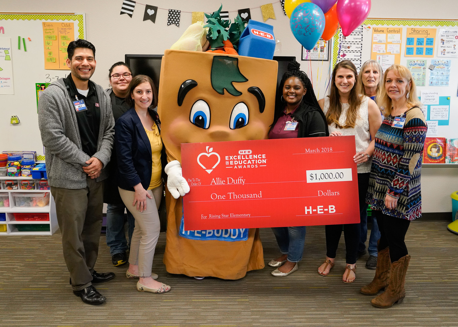 Allie Duffy poses with a group of H-E-B employees with a check for $1,000 during a visit to her classroom prior to the final selection of winners in the H-E-B Excellence in Education Awards.