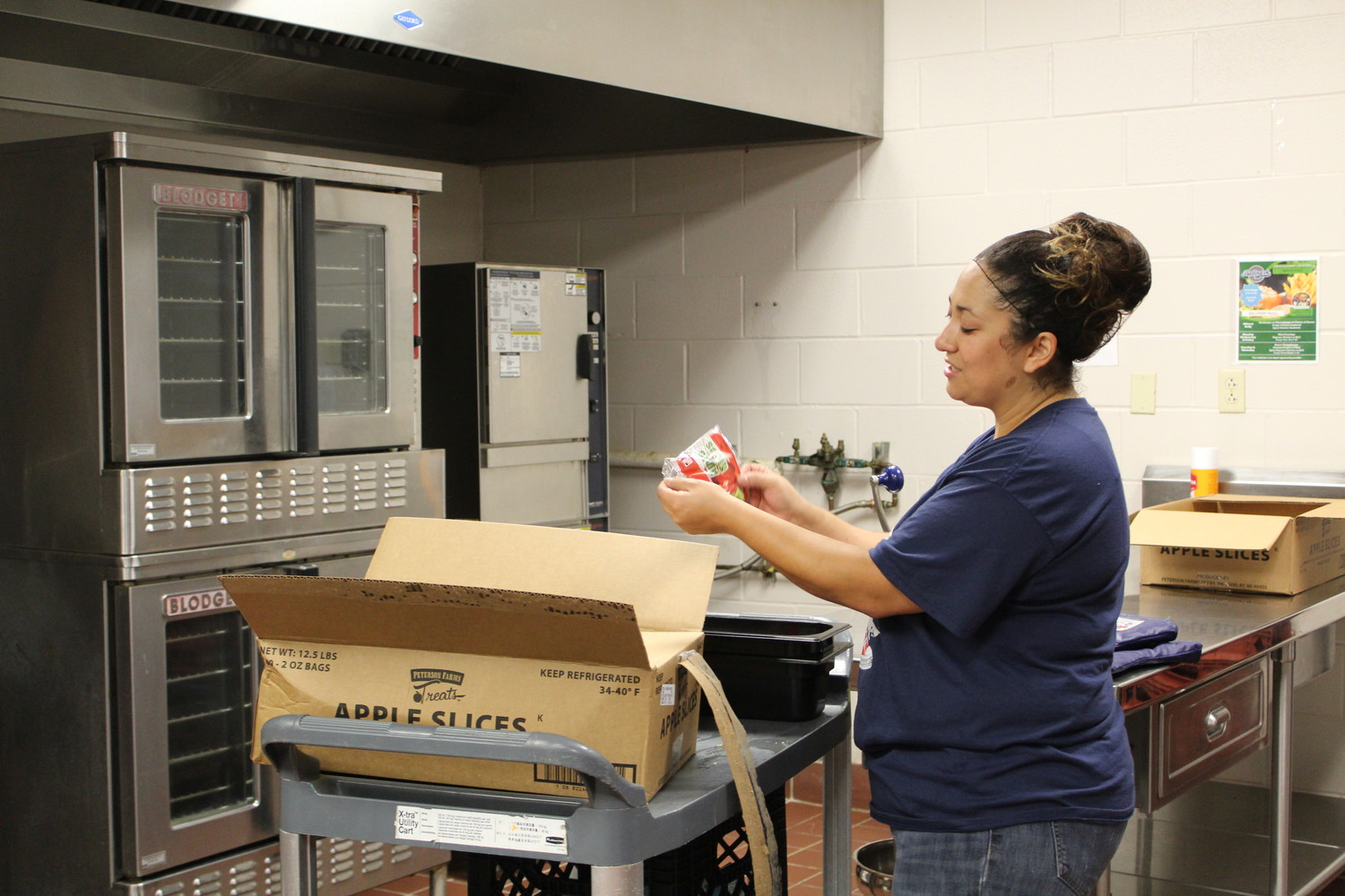 Naomi Flores, a server and cook, examines bags of fresh apple slices available for the free lunch program at Running Brushy Middle School on June 20.