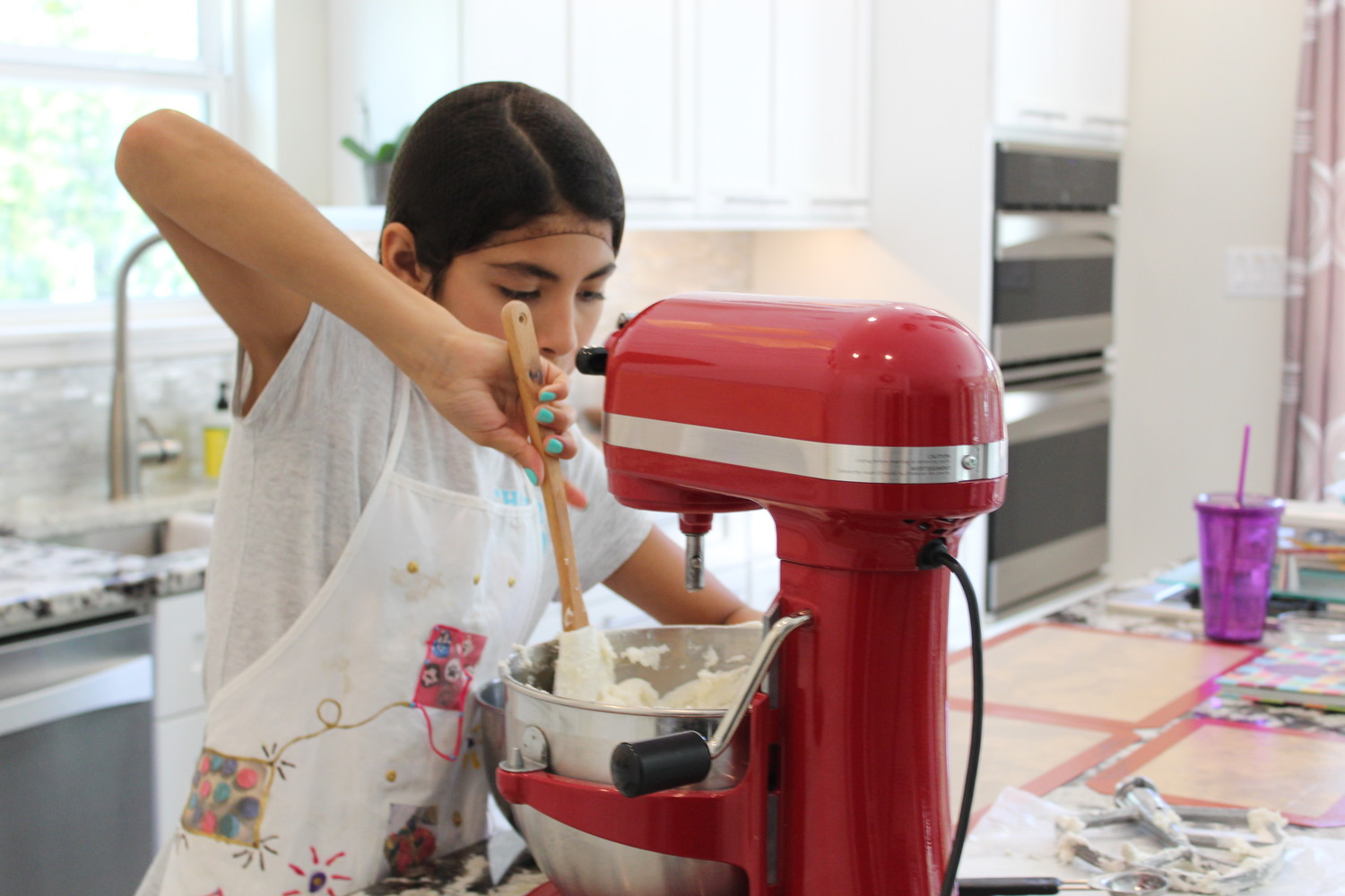 Ava Avila, 12, mixes frosting for cupcakes at her Round Rock home.