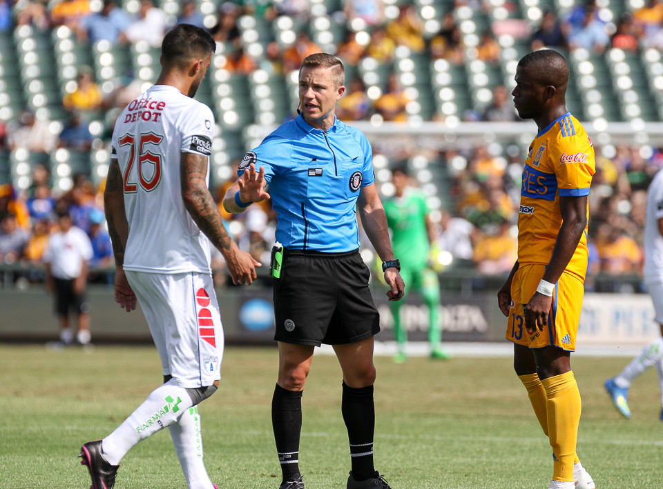 A game official talks with Pachuca's Robert Herrera (26) and Tigres' Enner Valencia (13) during a Liga MX friendly match between Tigres and Pachuca at Dell Diamond in Round Rock, Texas, on July 8, 2018.