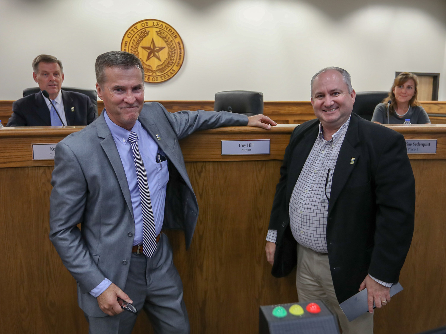 Leander Mayor Troy Hill poses in front of the dais at Pat Bryson Municipal Hall with former Mayor Chris Fielder during the July 5 city council meeting.