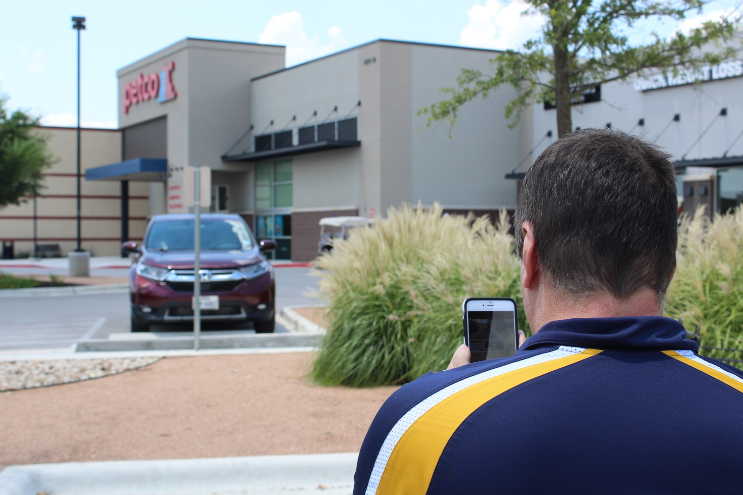 Parking Mobility director Mack Marsh uses the organization's app to collect data on accessible parking offenses at a retail development in Cedar Park Friday, July 6.