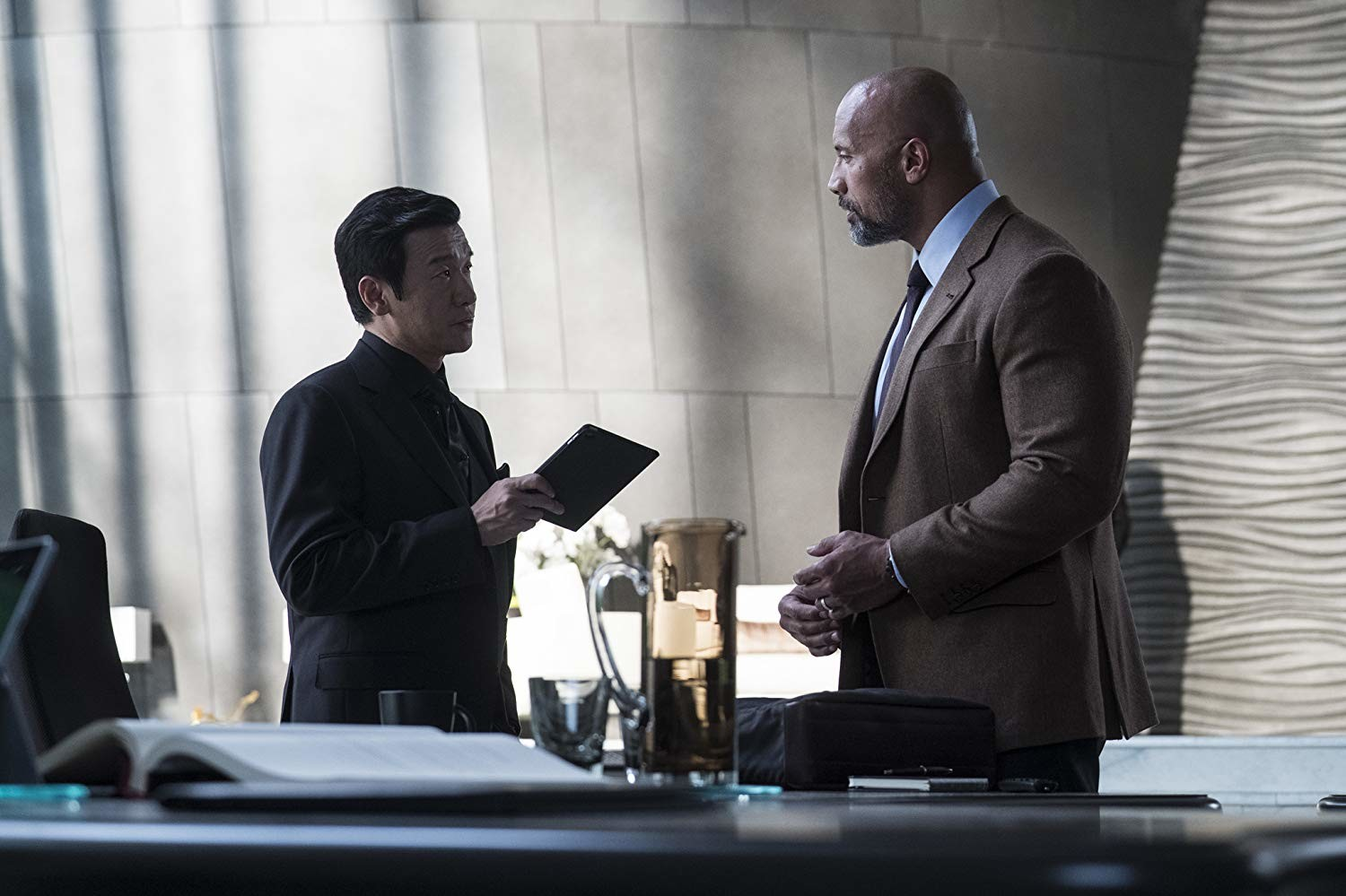 "Chin Han and Dwayne Johnson in ""Skyscraper,"" in area theaters now."