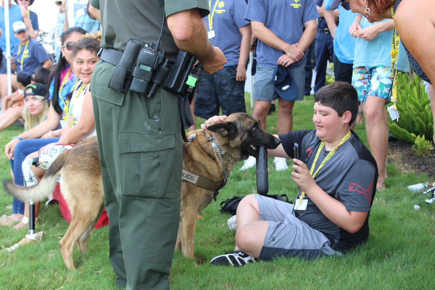 Sunshine Kid camper Connor Warfield, 14, of Katy, gives Travis County Sheriff's Office K-9 Bobek a well-deserved pat after demonstrating his abilities with narcotic searches and criminal takedowns.
