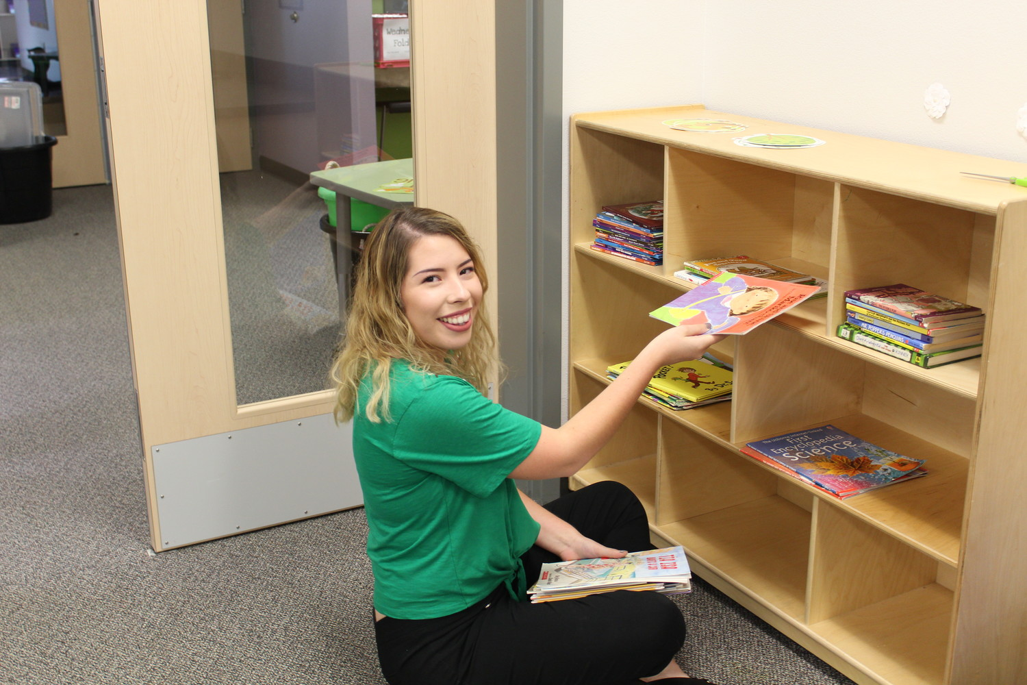 New Camacho Elementary teacher Elinore Ramos organizes books in her second grade classroom in preparation for the new school year.