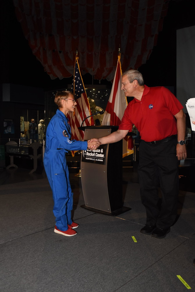 Eleven-year-old Mason Azios, of Leander, shakes hands with former astronaut Larry DeLucas during Space Camp's graduation ceremony July 19 in Huntsville, Ala.