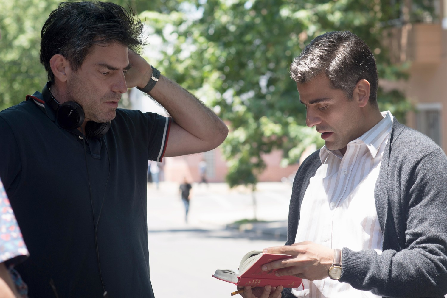 "Chris Weitz (left) goes over a scene from ""Operation Finale"" with star Oscar Isaac."