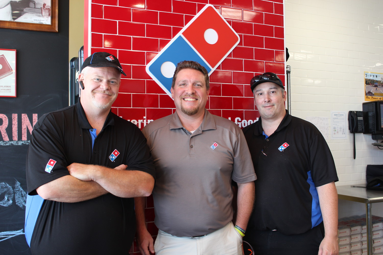 Domino's chef Anthony Walters, (left) franchisee Ike Coronis (middle) and driver Jason Sirak stand together at the Domino's pizza theater restaurant in Jonestown.