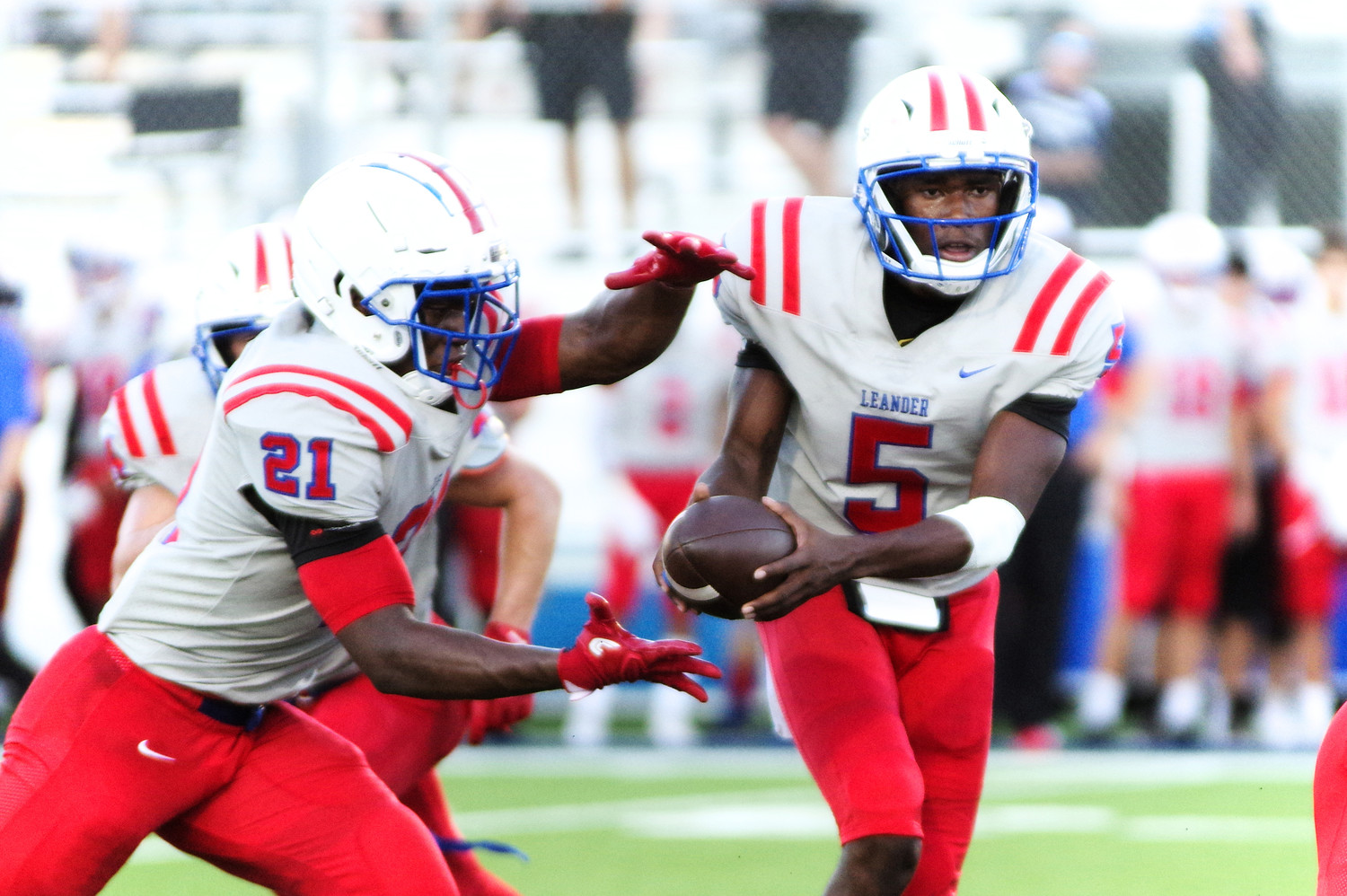 Leander high School Quarterback Rashad Cater (5) hands off to Runningback Xavier Dotson (21) against Weiss at the Pfield August 30, 2018.