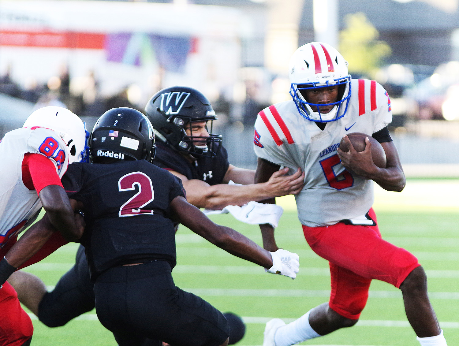 Leander High School Quarterback Rashad Carter (5) avoids a sack as he runs to the outside against Weiss at the Pfield August 30, 2018.