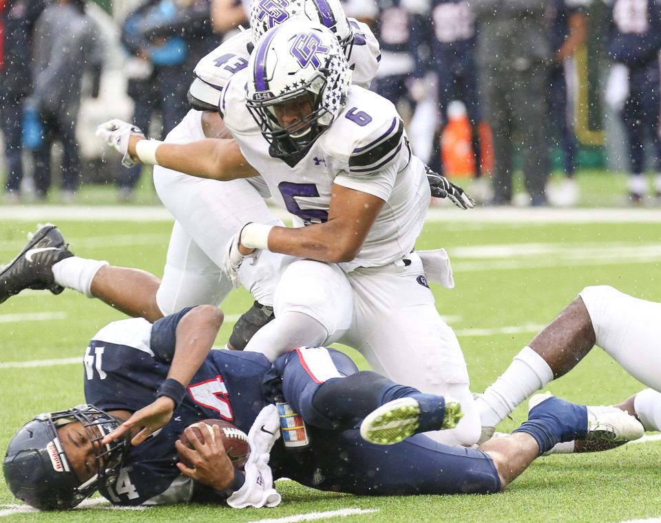 Cedar Ridge Raiders junior defensive lineman Edge Dillard-Williams (6) throws Allen Eagles quarterback Grant Tisdale (14) to the ground for a sack during the Class 6A Division I state semifinal game between Allen High School and Cedar Ridge High School at McLane Stadium in Waco, Texas, on December 16, 2017.