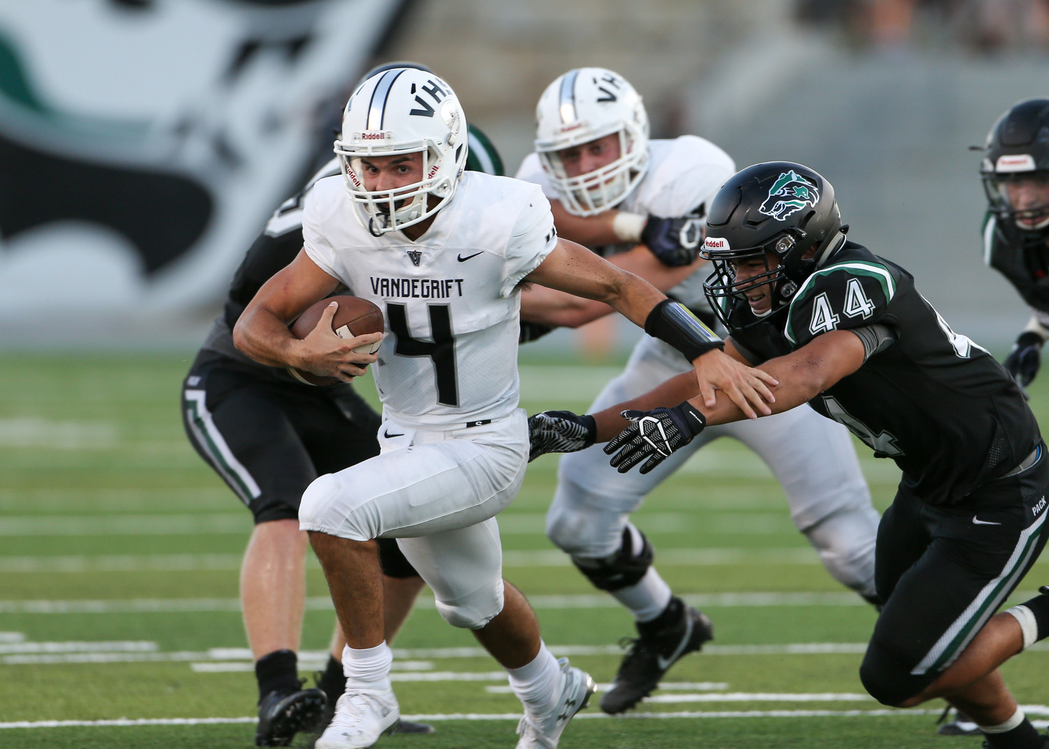 Vandegrift Vipers junior quarterback Dru Dawson (4) eludes Cedar Park Timberwolves senior linebacker Noah Morales (44) during a high school football game between the Cedar Park Timberwolves and the Vandegrift Vipers on Friday, Aug. 31, 2018 in Cedar Park, Texas.