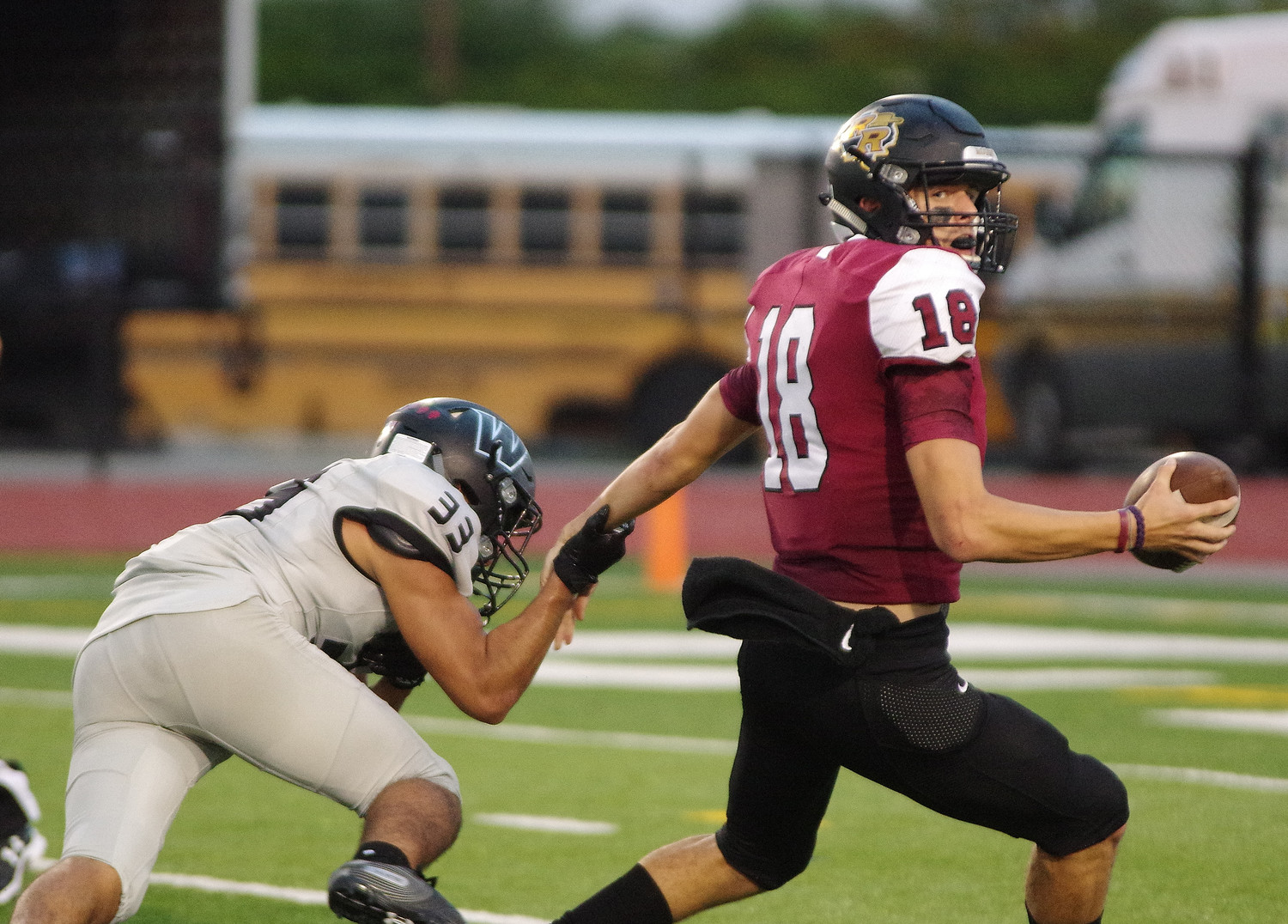 Rouse High School quarterback Ethan Moore (18) comes out of the pocket under pressure against Weiss at Bible Stadium on September 13, 2018.