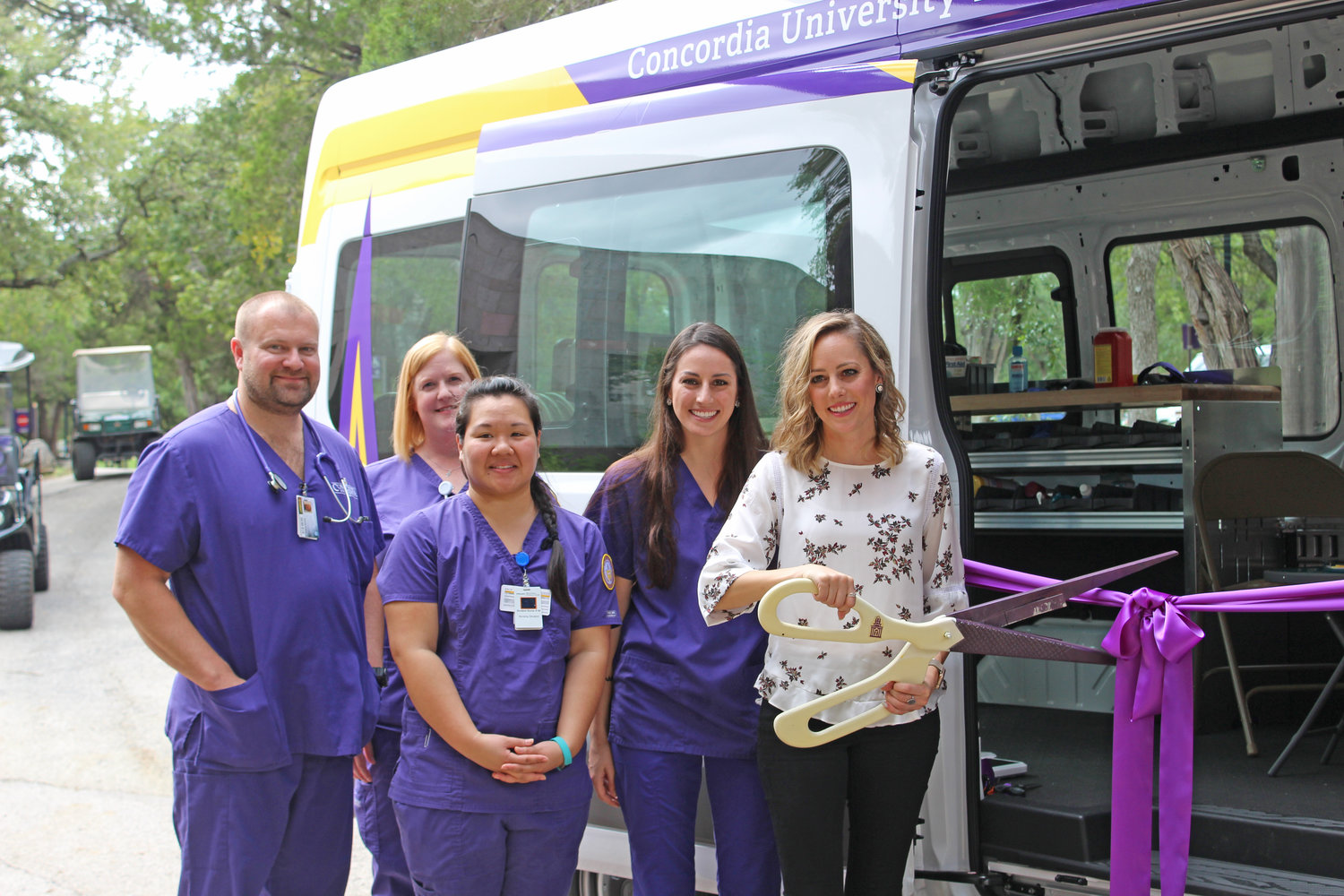 From left to right, Darrell Kalina, Amy Schneberger, Ann Marie Nguyen, Haylee Rowlette and Caitlin Rowlette stand together and prepare to cut the ribbon to Concordia's new nursing van on Sept. 28, 2018.