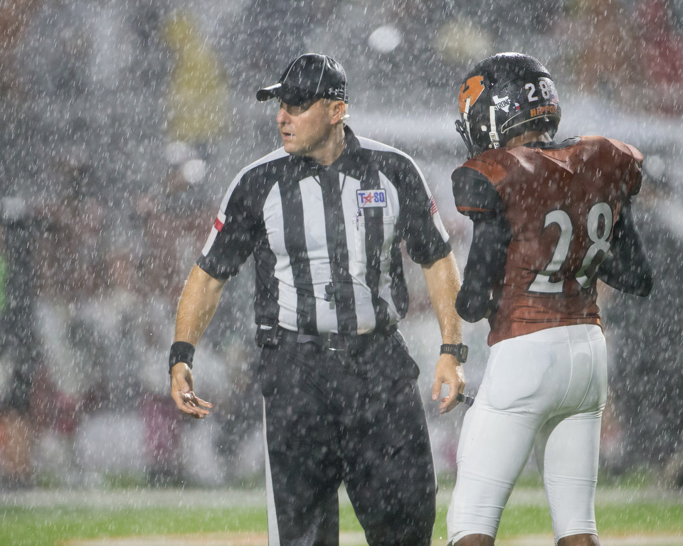A game official hands the ball to Hutto Hippos junior kicker Kendall Williams (28) during a downpour at a high school football game between Hutto and Cedar Park on Friday, Oct. 19, 2018 at Hippo Stadium in Hutto, Texas.