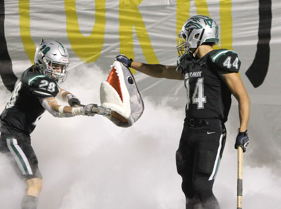 Cedar Park Timberwolves Jackson Rogers (28) and Noah Morales (44) take the field with a fake shark head before the start of a high school football playoff game between Cedar Park and the Shadow Creek Sharks at Merrill Green Stadium on Friday, Nov. 23, 2018 in Bryan, TX.