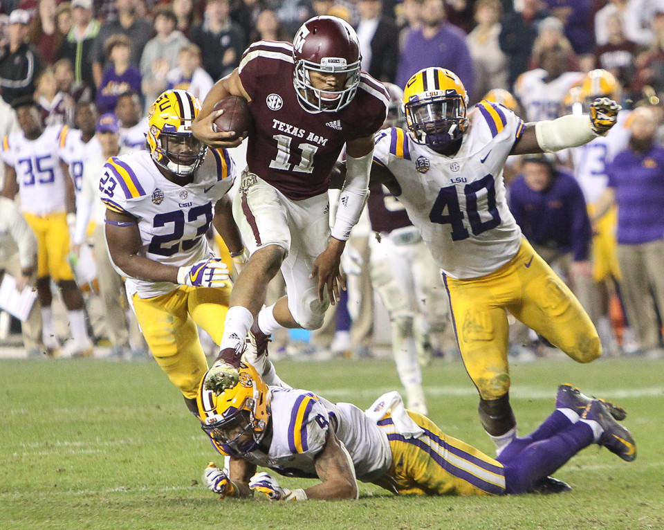 Texas A&M Aggies quarterback Kellen Mond (11) leaps a defender on a carry during overtime of an NCAA college football game between Texas A&M and LSU at Kyle Field on Sunday, Nov. 25, 2018 in College Station, TX.