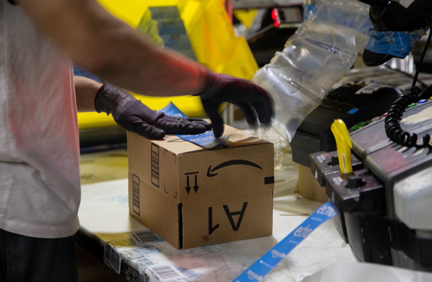 A worker tapes a box while packing items on Cyber Monday at the Amazon Fulfillment Center on Nov. 28, 2016 in San Bernardino, Calif.