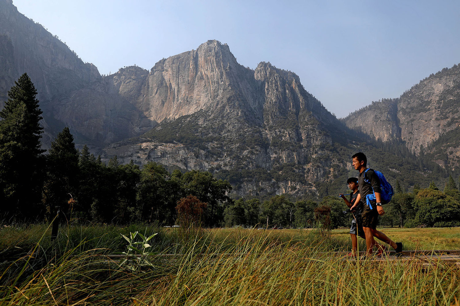 Guests make their way past Columbia Rock in Cook's Meadow in Yosemite, Calif., on Tuesday, Aug. 14, 2018. (Gary Coronado/Los Angeles Times/TNS)