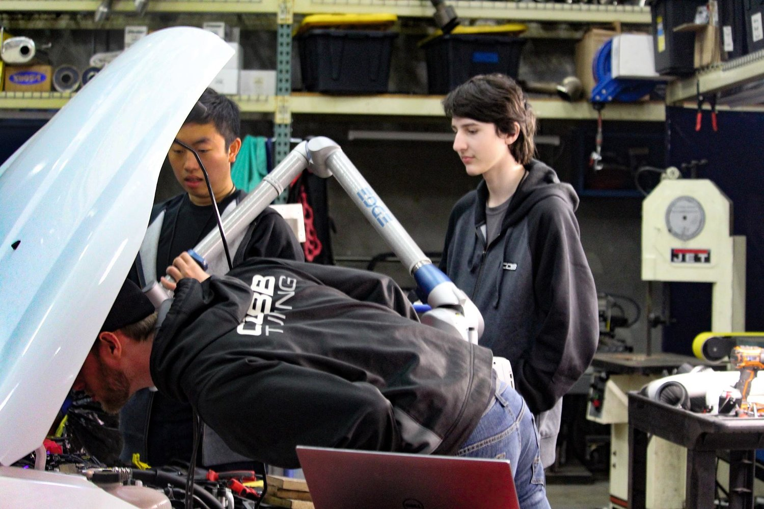 Vandegrift High School seniors Alex Tan (left) and Phillip Branca (right), observe COBB Tuning employee Paul Geyman during Leander ISD's COOL Week.