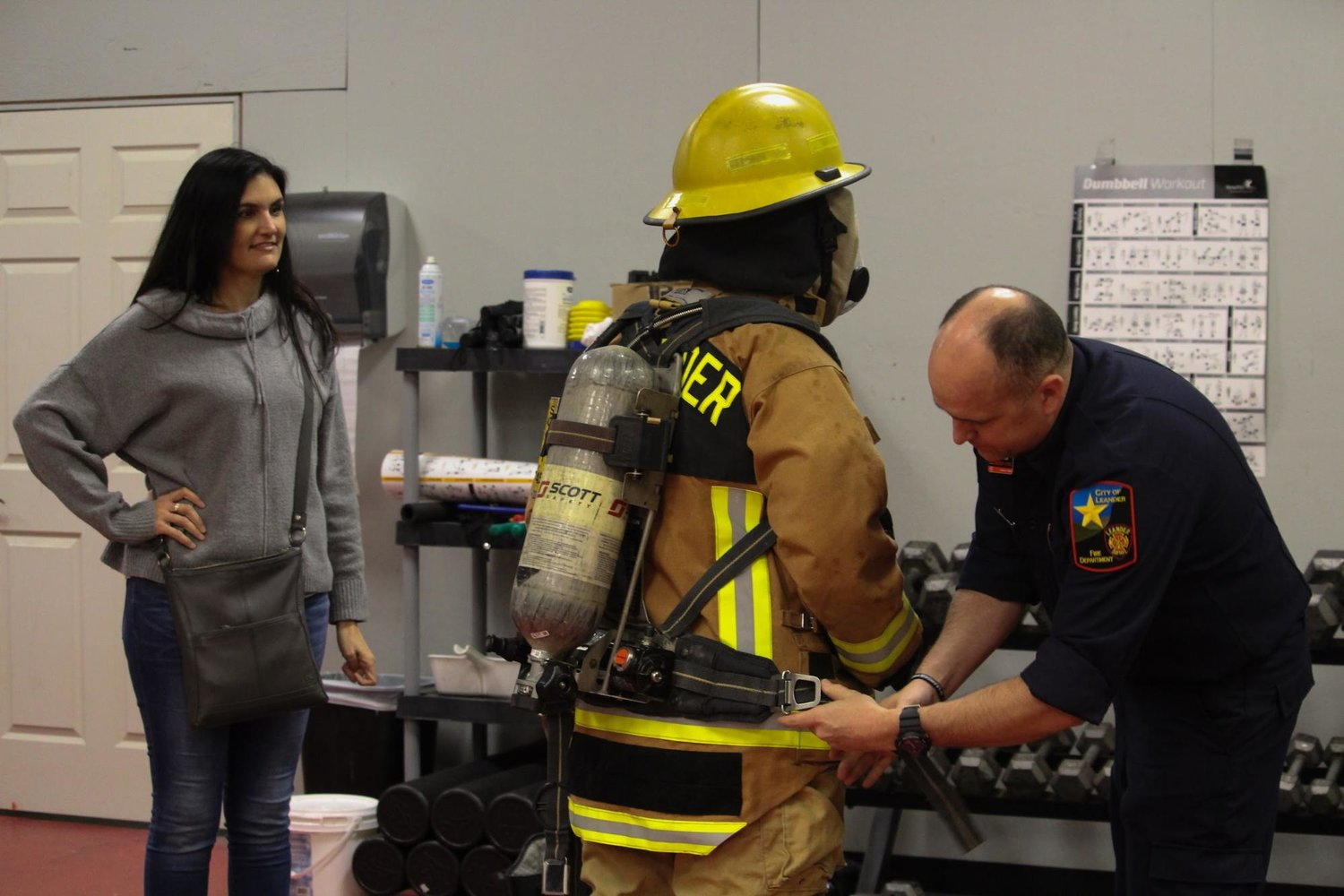 Glenn High School college and career transition coordinator (left) observes Leander Fire Department probationary firefighter Russell Summers fitting GHS senior Mia Crane into a set of 'turnout gear' during a COOL Week assignment with LFD.