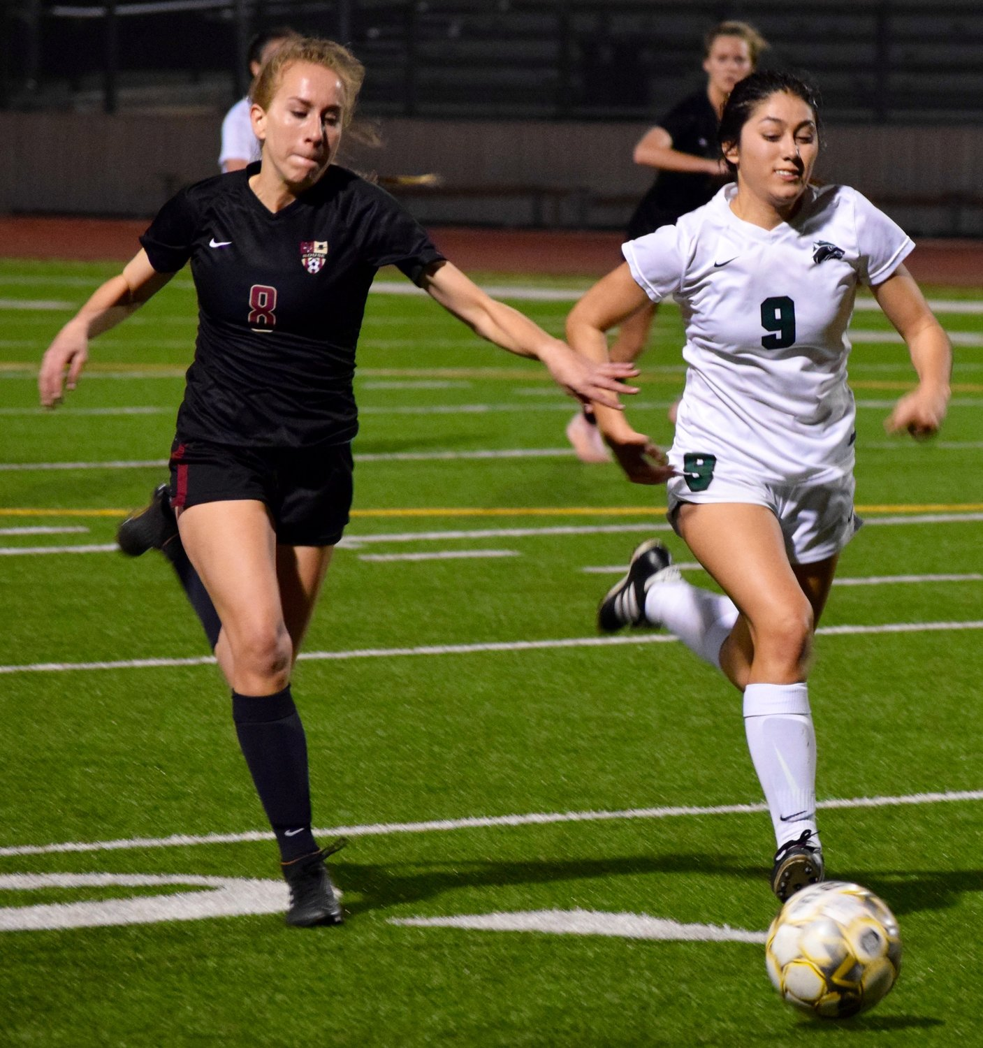 Rouse's Emma Metcalf, left, and Cedar Park's Maria Rico run for the ball Friday night at Rouse High School. The Lady Timberwolves beat the Lady Raiders 4-1.