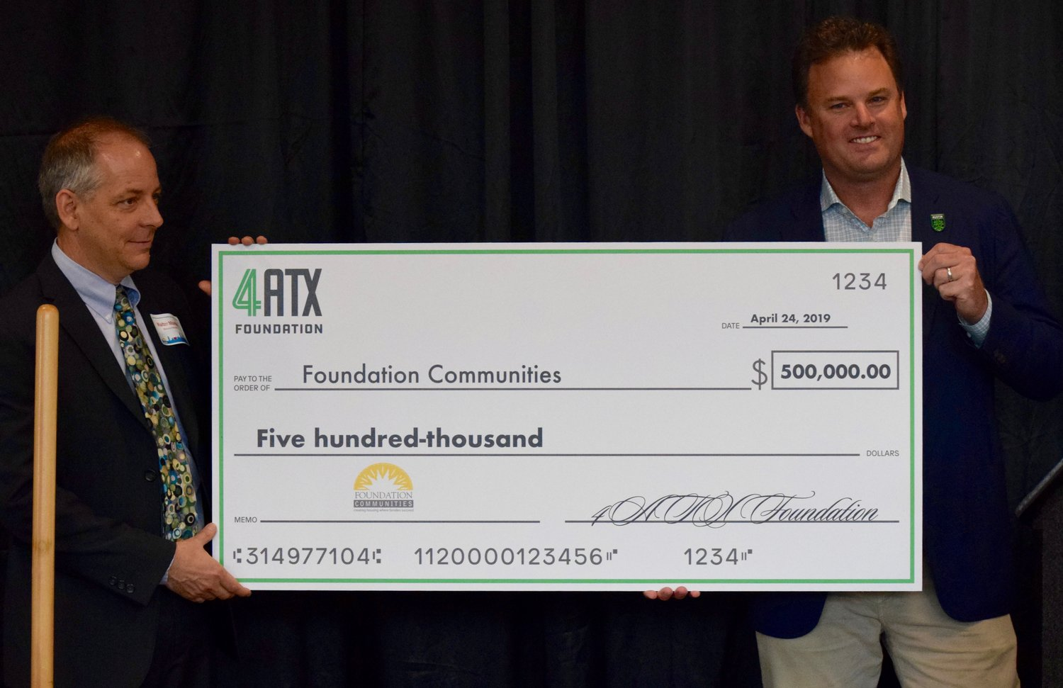 Austin FC chairman and CEO Anthony Precourt presents Foundation Communities executive director Walter Moreau with a check for $500,000 at a ceremonial groundbreaking last week.